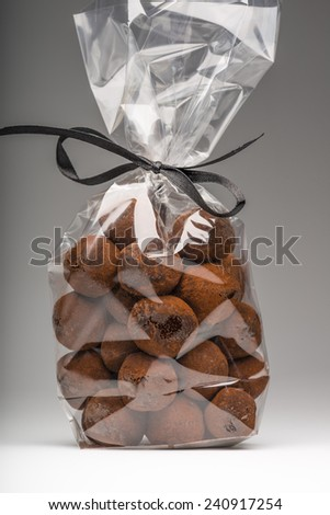 Beautiful and delicious chocolate truffles bag with elegant black ribbon on grey background. Shooting in studio. - stock photo