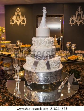 Beautiful and delicious wedding cake sitting in a wedding reception. - stock photo