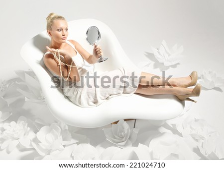 Beautiful and elegant girl with pearls .Beautiful young woman sitting on a white chair surrounded by stylish white flowers  - stock photo