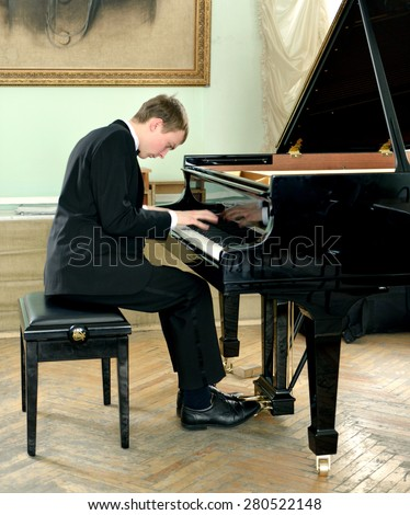 Beautiful and elegant young pianist plays black grand piano - stock photo