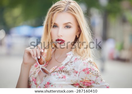 Beautiful  and fashion blonde young woman with sunglasses walking in the city. Summer photo - stock photo