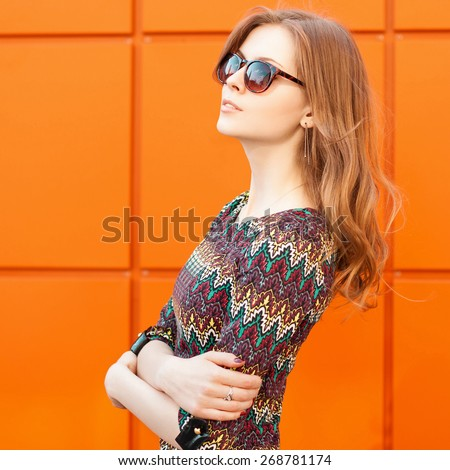 Beautiful and fashion girl  in summer sunny day, close-up portrait. Background of a bright orange wall. - stock photo