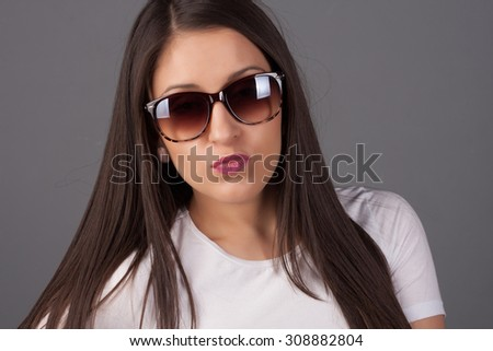 Beautiful and fashion portrait of a girl in sunglasses. Close-up portrait, studio shot. Close up fashion model wearing sunglasses