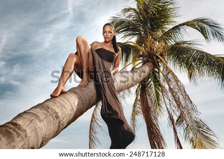 Beautiful and fashion young woman laing down coconut palm on beach  - stock photo