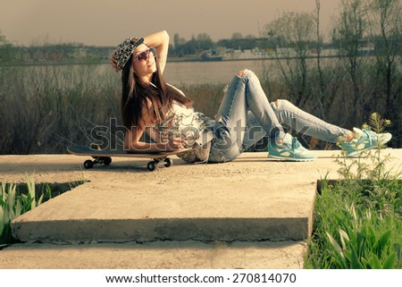 Beautiful and fashion young woman posing with a skateboard near river backlit. Instagram color. - stock photo