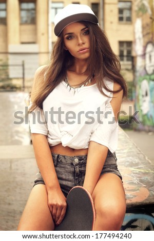 Beautiful and fashion young woman posing with skateboard. Sexy girl sitting in t-shirt,  shorts and cap. Outdoor portrait. - stock photo