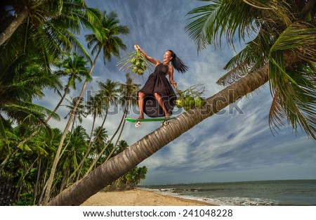 Beautiful and fashion young woman riding down coconut palm with a skateboard on beach  - stock photo