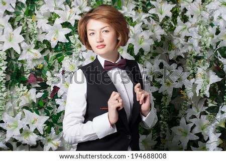 Beautiful and fashion young woman  with his son near the wall of flowers