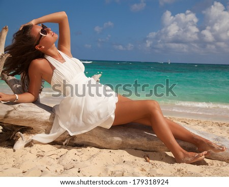 Beautiful and fashion young woman with long legs in white dress, posing in the Tropical beach - stock photo
