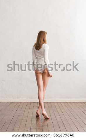 Beautiful and fit woman in white panties posing near the wall. - stock photo