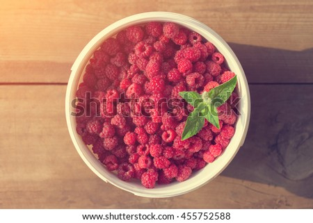 Beautiful and fresh raspberries with mint in white plastic bucket on wooden floor background