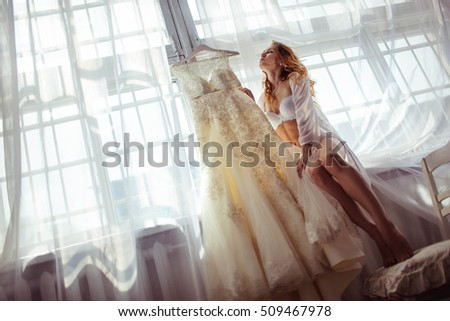 beautiful and gentle bride in underwear sits near her wedding dress