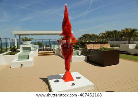 Beautiful and graceful red kinetic sculpture on an oceanfront terrace - stock photo