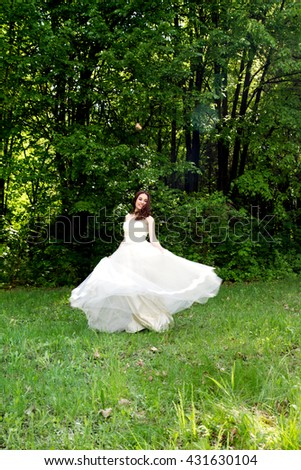 Beautiful and happy bride turned in a forest glade - stock photo