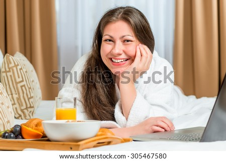 beautiful and happy girl on the bed with a tray of food - stock photo