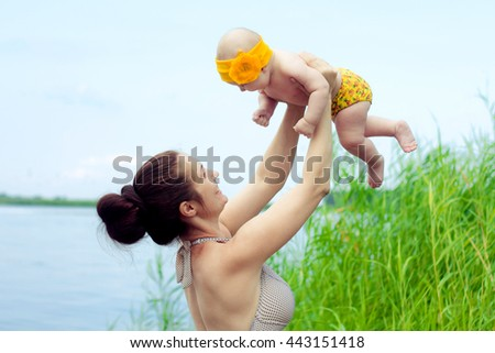 Beautiful and happy mom and daughter bathe. The concept of maternal parental love. Sunny summer day. Relax on the beach of the river - stock photo