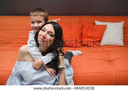 beautiful and happy mom and son sitting on the floor