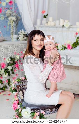 Beautiful and happy mom brunette in a white dress holding on the handles a little girl daughter on the background of the spring interior with flowers - stock photo