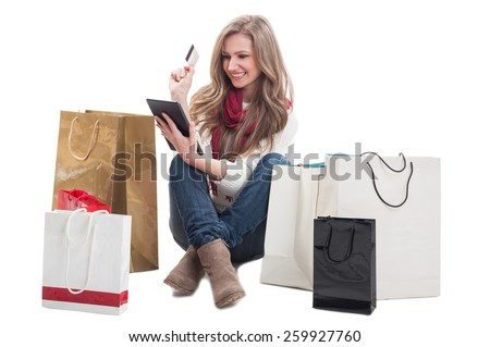Beautiful and happy shopping woman holding credit or debit card and tablet with shopping bags arround her - stock photo