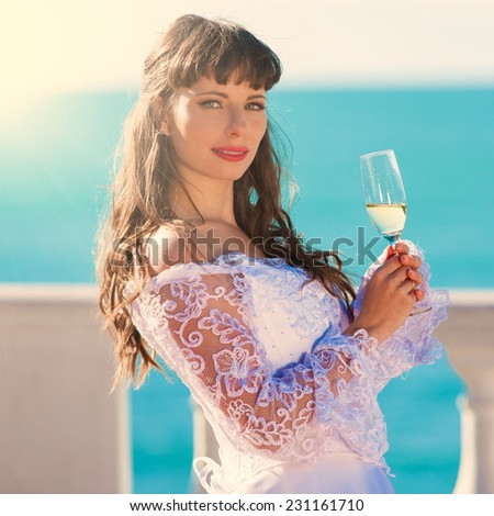 beautiful and happy smiling  brunette bride in white lacy satin dress european style with  glass of champagne sea background - stock photo