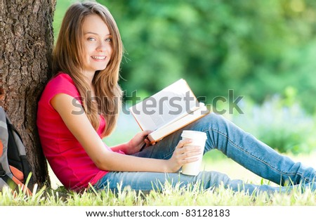 beautiful and happy student girl sitting on green grass under the tree, smiling and looking into the camera, book in one hand and cup of coffee in the other. Summer or spring green park in background
