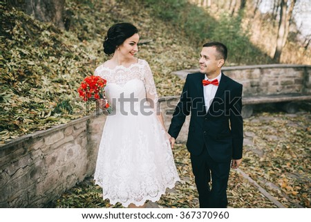 Beautiful and happy wedding pair in a lovely autumn sunny bright day.