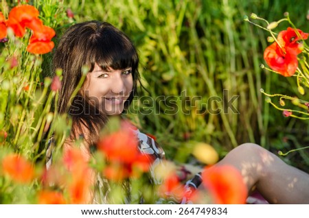 beautiful and happy woman lying in field of poppy flowers