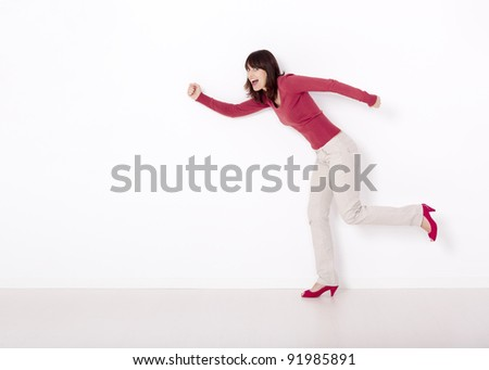 Beautiful and happy woman simulating she's running against a white wall - stock photo