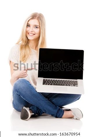 Beautiful and happy woman working and pointing to the laptop, isolated over white background - stock photo