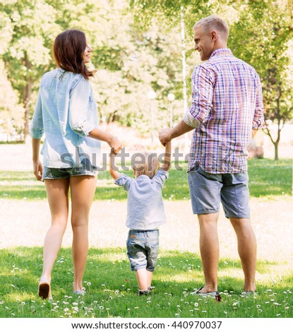 Beautiful and happy young couple having a great time with son while walking in the park.