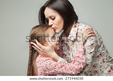 Beautiful and happy young mother kissing her small daughter. Isolated on white background. - stock photo