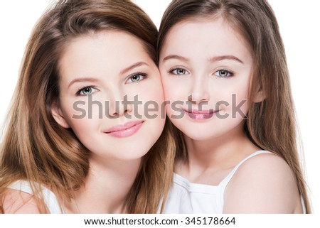 Beautiful and happy young mother with a small daughter 8 years embrace each other at studio  - stock photo
