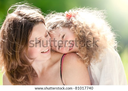 Beautiful and  happy young mother with her daughter on her shoulder. Both smiling, summer park in background - stock photo