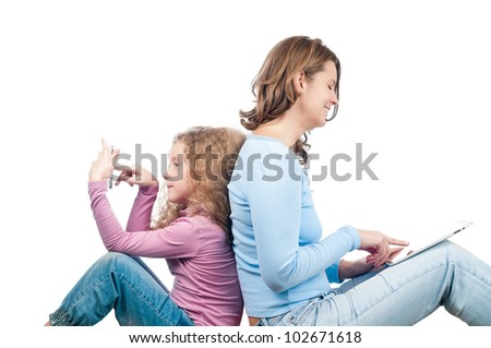 Beautiful and happy young mother with her small daughter sitting on the floor back to back and using tablet and phone. Both smiling. Isolated on white background. - stock photo