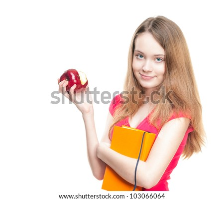 Beautiful and happy young student girl eating red apple and holding book in her hands. Looking into the camera. Isolated on white background. - stock photo
