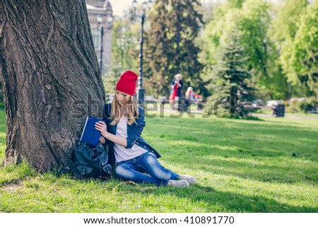 Beautiful and happy young student girl in red hat put the book in a backpack, purse sitting on green grass under the tree near the campus, university school, education. Summer or spring green park - stock photo