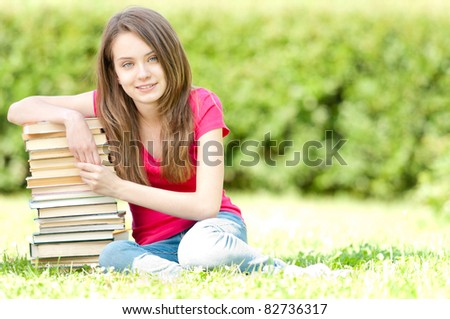 beautiful and happy young student girl sitting on green grass, pile of books under her hand, smiling and looking into the camera. Summer or spring green park in background - stock photo