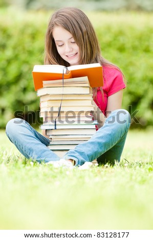 beautiful and happy young student girl sitting on green grass, pile of books under her hands, smiling and reading book. Summer or spring green park in background - stock photo
