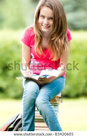 beautiful and happy young student girl sitting on pile of books, holding exercise book in her hands, smiling and looking into the camera. Summer or spring green park in background - stock photo