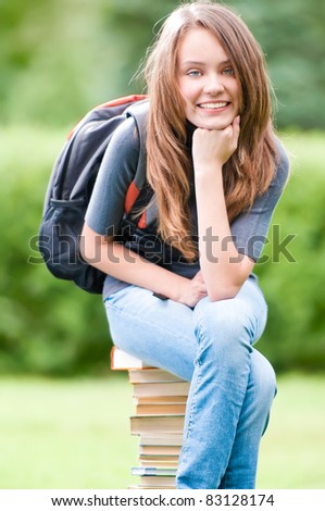 beautiful and happy young student girl sitting on pile of books, smiling and looking into the camera. Backpack on her shoulder. Summer or spring green park in background - stock photo