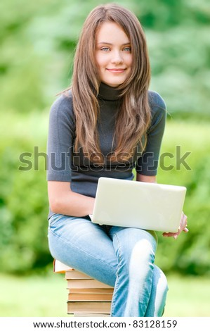 beautiful and happy young student girl sitting on pile of books with laptop computer, smiling and looking into the camera. Summer or spring green park in background - stock photo