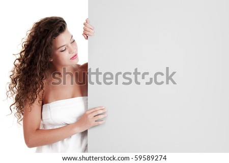 Beautiful and happy young woman isolated on white holding a white billboard - stock photo
