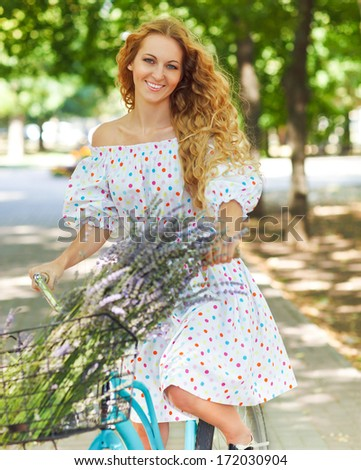 Beautiful and happy young woman on bicycle on the summer park in background - stock photo