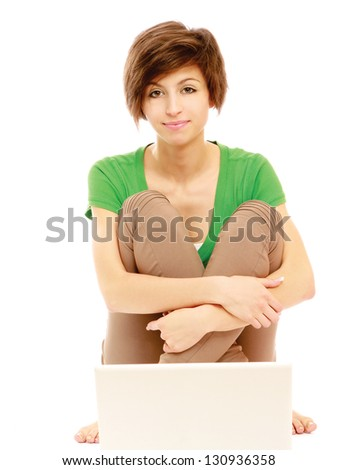 Beautiful and happy young woman sitting on floor and using a laptop - stock photo