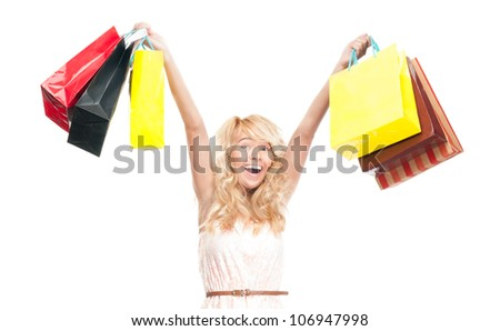 Beautiful and happy young woman standing isolated on white background with shopping bags in her hands over her head. Looking into the camera and laughing.