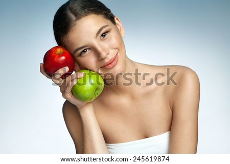 Beautiful and Healthy, natural organic raw fresh food concept / portrait of mixed race Latina Caucasian girl with two apples in her hand over blue backdrop  - stock photo