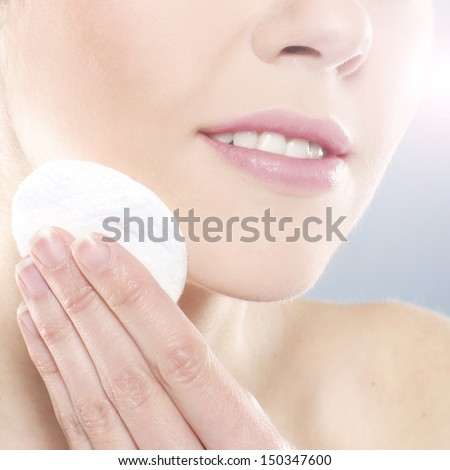 Beautiful and healthy young woman cleaning her face - stock photo