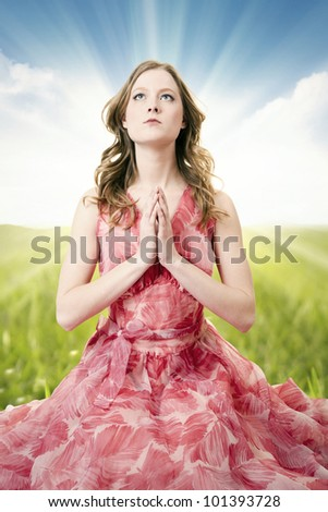 Beautiful and innocent woman praying on the grass. - stock photo