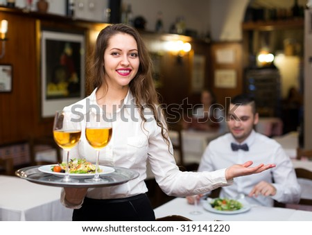 Beautiful and joyful waitress serving in a restaurant. She is holding a full tray in her hand and smiling - stock photo