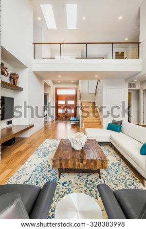 Beautiful and large living room interior with hardwood floors and vaulted ceiling in new luxury home. View of entryway and loft style second story area - stock photo